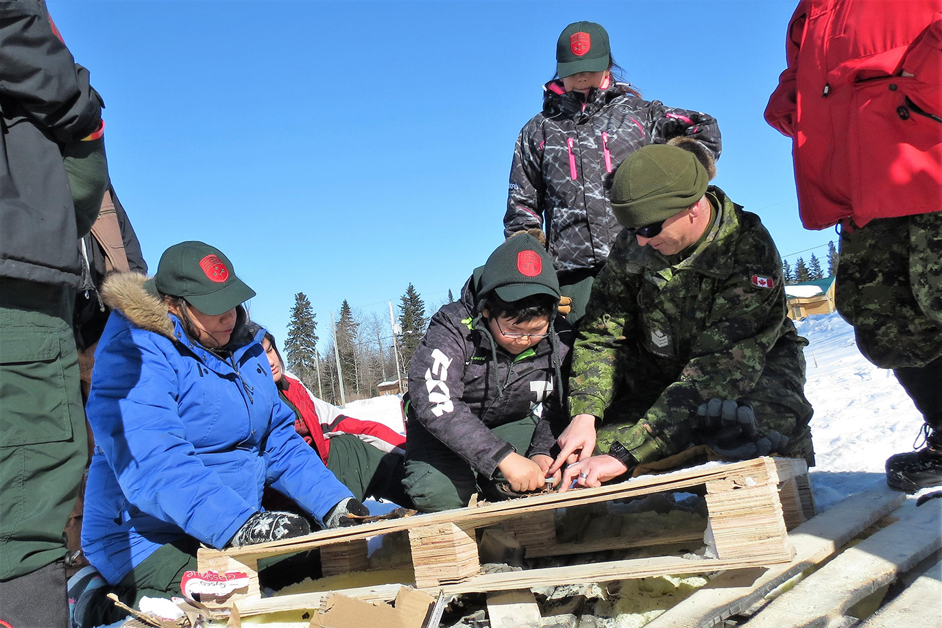 Sergeant Scott Hooper, a Canadian Army instructor helps a Junior Canadian Ranger to use a magnesium and a striker to start a fire. Photo : Sergeant Peter Moon, Canadian Rangers. ©2017 DND/MDN Canada.