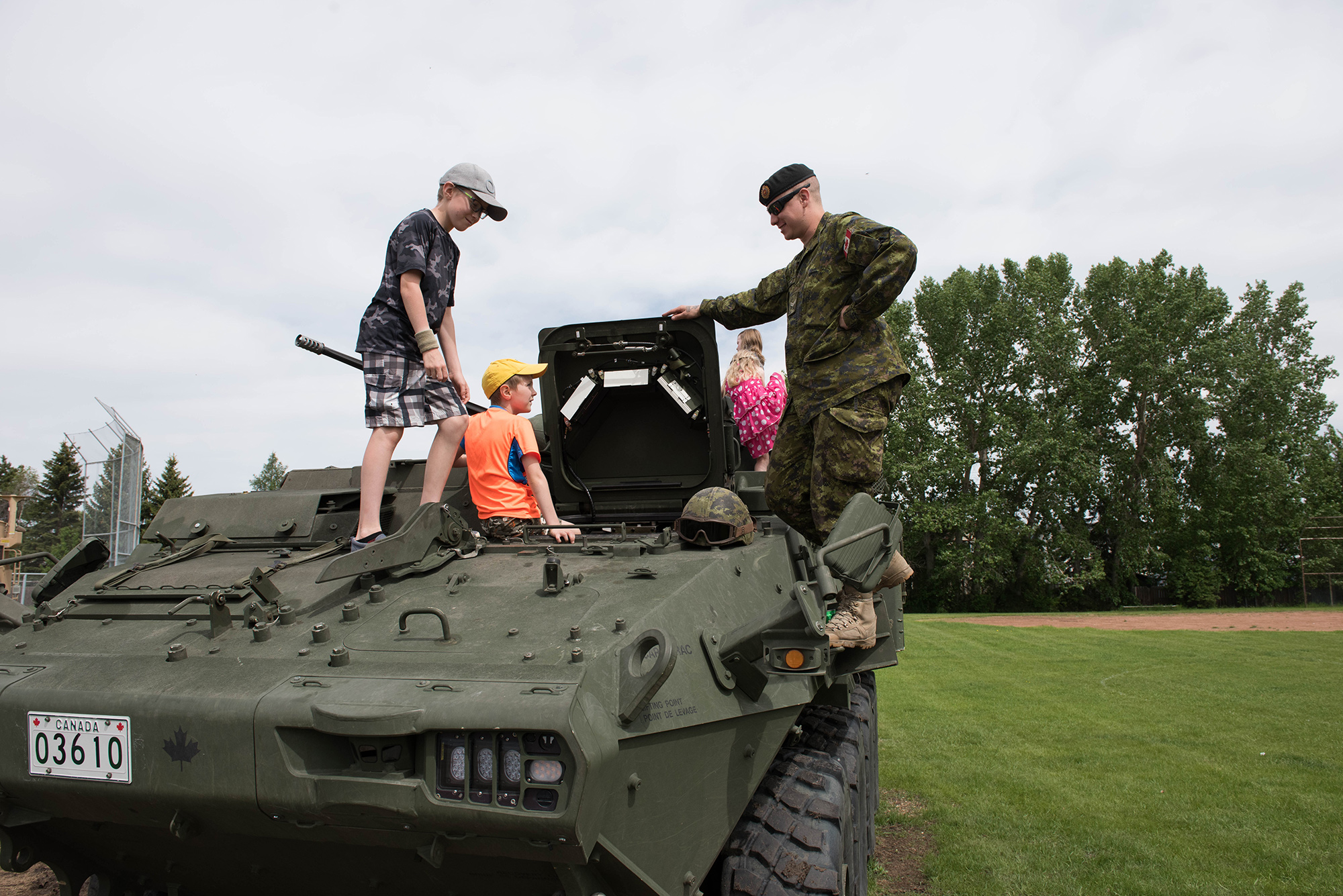 A soldier with 1 Combat Engineer Regiment shows the children of Bon Accord the inside of a Light Armoured Vehicle in Bon Accord, Alberta on June 3, 2017. Photo: Master Corporal Andrew Davis, 3rd Canadian Division Support Base Edmonton. © 2017 DND-MDN Canada