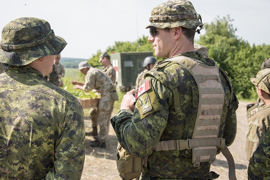 Major Christopher Hartwick (right) of Joint Task Force - Ukraine  listens in as officers of the Ukrainian Armed Forces brief their troops prior to a live-fire training scenario at the International Peacekeeping and Security Centre in Starychi, Ukraine, on June 16, 2017.