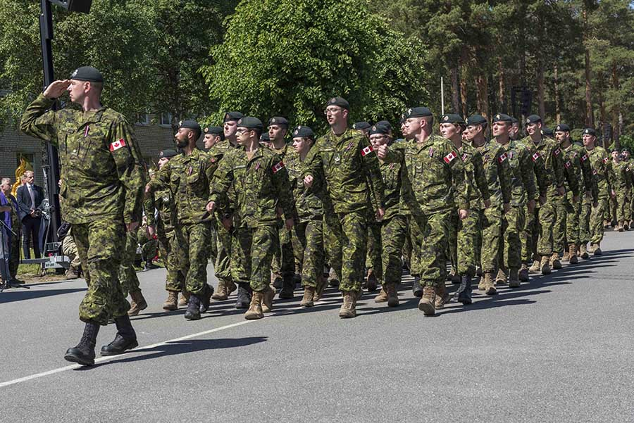 The first guard of Canadian troops, led by Major Troy Leifso, salute as they conduct a march past during the ceremony marking the establishment of the NATO enhanced Forward Presence Battlegroup at Camp Ādaži, Latvia on June 19, 2017.