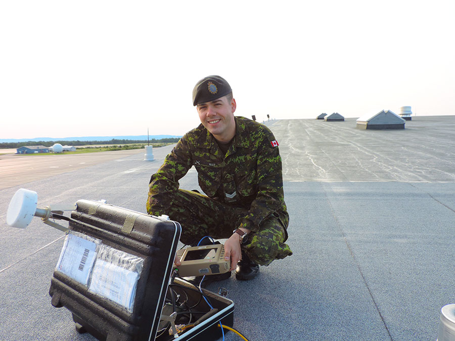 Corporal Nicholas Huot sets up the 5I Rover unit on a roof.