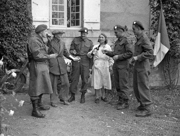 Members of the 3rd Field Security Section, Canadian Intelligence Corps, share a glass of wine with a French couple