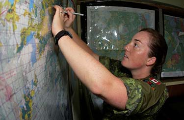 Captain Sarah Heer, Artillery Officer, plots coordinates on a map as the Disaster Assistance Team Company Operations Officer during Operation HESTIA in Haiti in 2010. Photo: provided by Lieutenant-Colonel Sarah Heer.