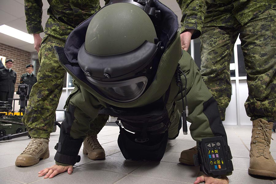 A cadet from 2250 The Muskoka Pioneers Royal Canadian Army Cadets does push-ups in an Explosive Ordnance Disposal bomb suit in Bracebridge, Ontario on October 18, 2017 during Exercise ARDENT DEFENDER 2017.