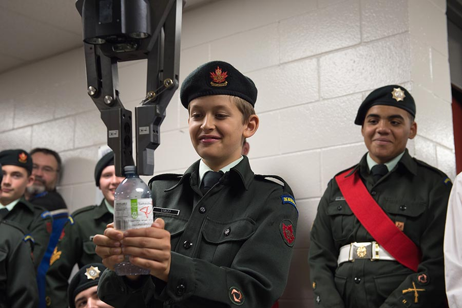 A Teodor Remote Operated Vehicle opens a water bottle for a cadet as part of an Explosive Ordnance Device equipment demonstration to 2250 The Muskoka Pioneers Royal Canadian Army Cadets in Bracebridge, Ontario, 2017 during Exercise ARDENT DEFENDER 2017.