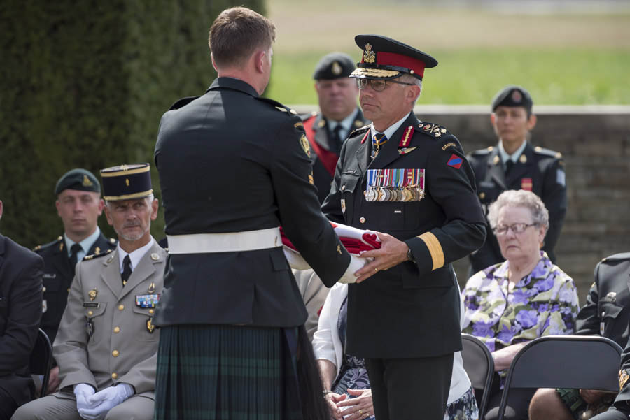 On behalf of the Canadian Army, the regiment and family, Lieutenant-General Paul Wynnyk, Commander of the Canadian Army receives the ceremonial flag from the coffin of an unknown Canadian soldier who was laid to rest with military honours at Canadian Cemetery No. 2 in Neuville-St. Vaast, France on August 23, 2017. Photo: Corporal Andrew Wesley, Army Public Affairs. ©2017 DND/MDN Canada.