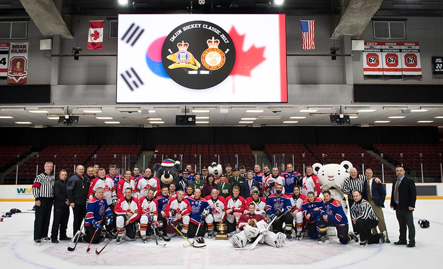 A group picture of all the participants from the 2017 Imjin Hockey Classic with the Imjin River Memorial Cup.