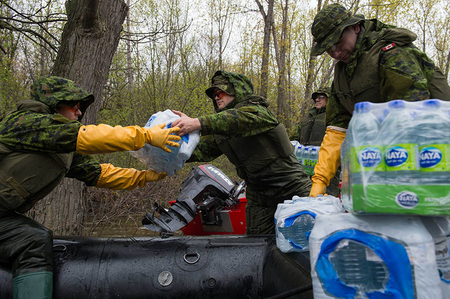 Reservists from 35 Canadian Brigade Group distribute water to residents on l'Île Mercier during Operation LENTUS, May 14, 2017. Assisting civilian authorities in responding to natural disasters is just one way Reservists serve. The Canadian Army Reserve is growing its ranks and offering, among other incentives, a Full-time Summer Employment Program.
