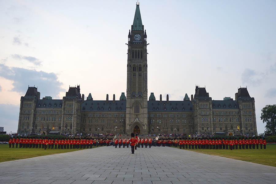 The Ceremonial Guard stands in front of the Peace Tower of the Parliament Buildings in 2014 as the sun sets during Fortissimo, the Canadian Army's showcase event that has occurred in July and August for more than 20 years.