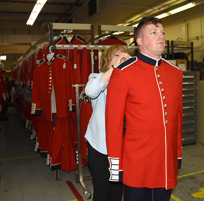 In a behind-the-scenes glimpse of events leading up to marching on Parliament Hill, a new member of the Ceremonial Guard proudly stands at attention while his scarlet uniform is fitted in Ottawa, Ontario in May 2017.