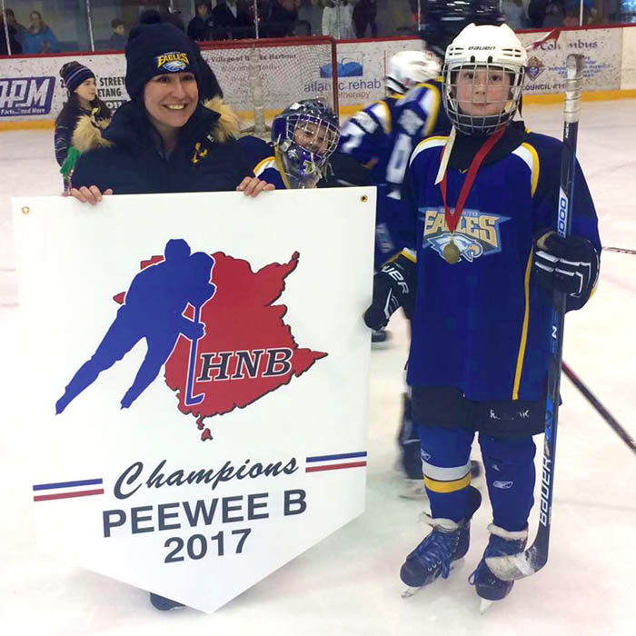 Sergeant Marie-Eve Martin celebrates with her son, Alex at age 11 at the Fundy Arena in Black's Harbour, New Brunswick. Alex, who plays centre, and his team were the Peewee competitive B champions in 2017. 