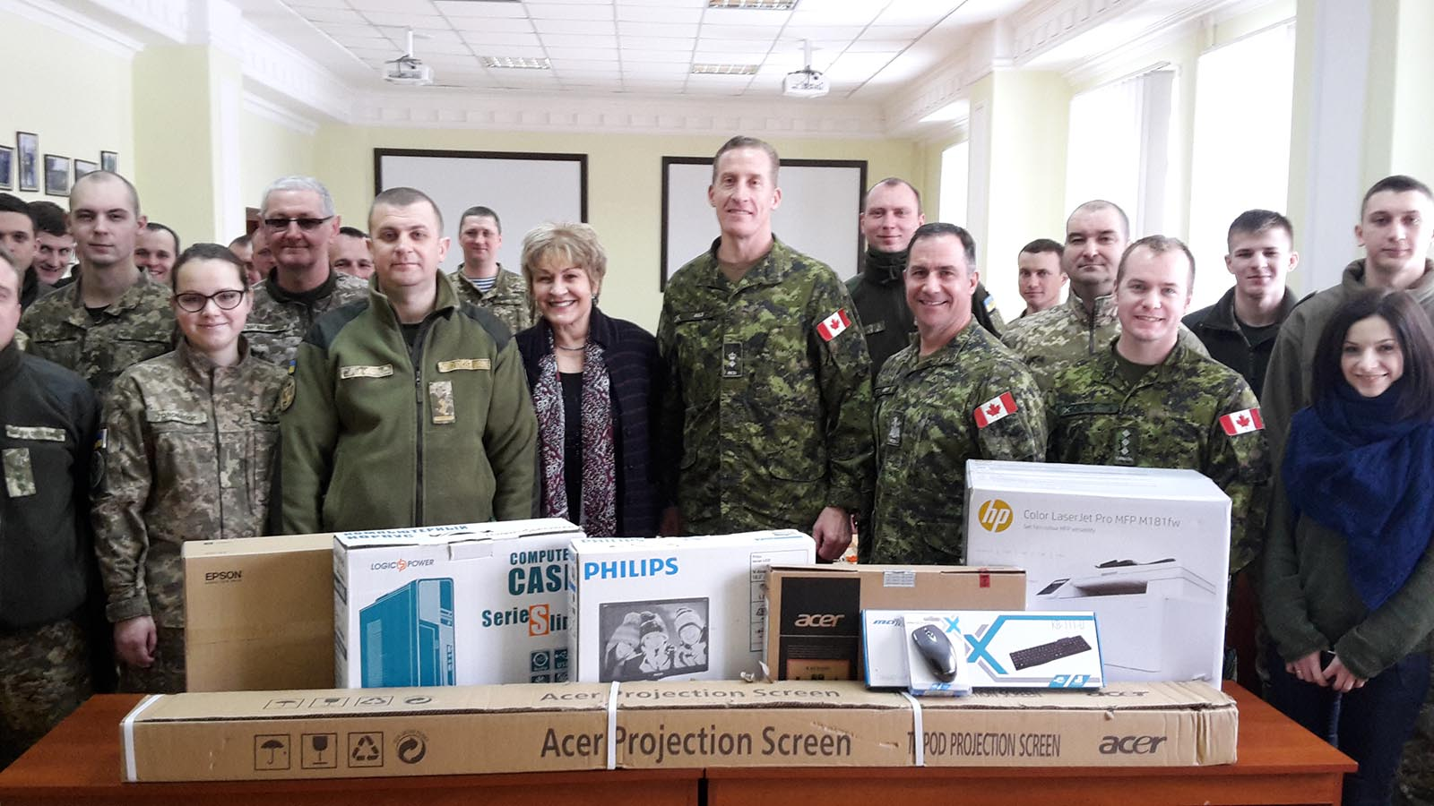 Lieutenant-Colonel Fraser Auld, Commander Joint Task Force - Ukraine (centre) stands with Roksolana Baran of the Canadian Forces Language School Detachment Saint-Jean, as they present language training equipment to the Ukrainian representatives. Photo: Provided by Roksolana Baran. ©2018 DND/MDN Canada.