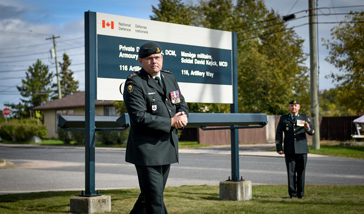 Lieutenant-Colonel Shawn Fortin, Commanding Officer of 38 Canadian Brigade Group (38 CBG) Artillery Tactical Group passes in front of the new armoury sign on September 29, 2018 following a ceremony to rename Ontario's Kenora Armoury in honour of the late Private David Kejick. In the background is 38 CBG Artillery Tactical Group Regimental Sergeant Major Chief Warrant Officer Todd Appel. Photo: Officer Cadet Natasha Tersigni, 38 Combat Brigade Group. ©2018 DND/MDN Canada.