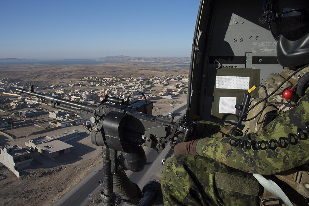 A door gunner on a CH-146 Griffon helicopter keeps vigilant watch during Operation IMPACT in northern Iraq on November 23, 2016.  Photo: Canadian Forces Combat Camera. ©2016 DND/MDN Canada.