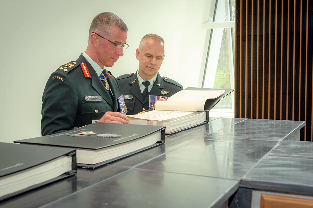 Lieutenant-General Jean-Marc Lanthier, Commander Canadian Army and Chief Warrant Officer Stu Hartnell, Canadian Army Sergeant Major, read one of the Afghanistan Memorial Books at the Afghanistan Memorial Hall at National Defence Headquarters (Carling) on May 13, 2019. Photo: Master Corporal Levarre McDonald, Canadian Forces Support Unit (Ottawa). ©2019 DND/MDN Canada.