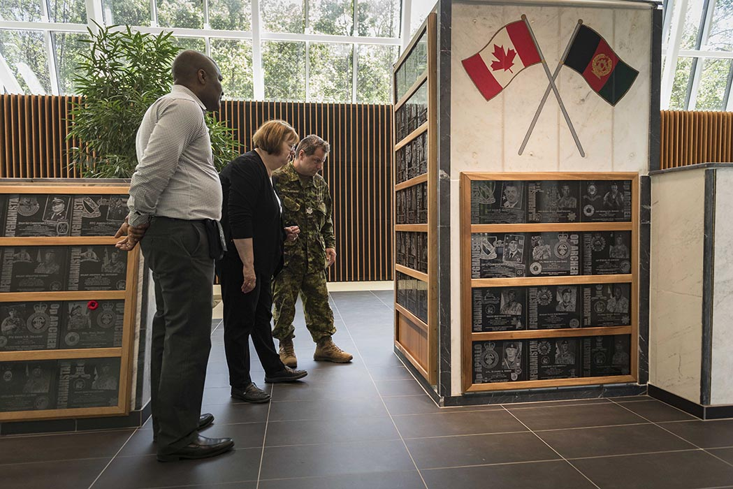 At the Afghanistan Memorial Hall in Ottawa, Ontario on June 11, 2019, visitors look at plaques commemorating Canadian and American military personnel who lost their lives in Afghanistan. Photo: Able Seaman Camden Scott, Army Public Affairs. ©2019 DND/MDN Canada.
