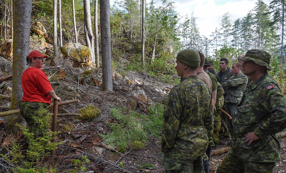 Canadian Ranger Jeanie Keays of the Powell River Canadian Ranger Patrol shows soldiers from 3rd Canadian Division how to select trees to cut down for shelters during the Enhanced Wilderness Survival Training course on September 26, 2019 in Coal Harbour on the North coast of Vancouver Island. Photo: 4th Canadian Ranger Patrol Group. ©2019 DND/MDN Canada.