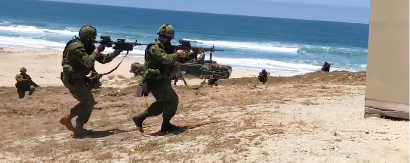Slide - Soldiers charge out of an armoured vehicle on to a beach